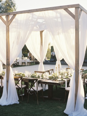 outdoor wedding reception with wooden structure and soft white drapery