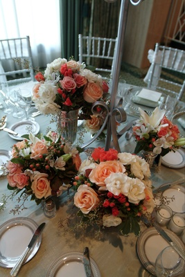 Orange and pink flower arrangements at base of candelabra