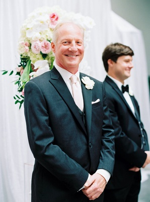 groom in charcoal gray black tuxedo pink tie smiling