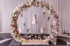 Wedding cake floating circle of flowers wreath candles at base drapery wedding ideas unique display
