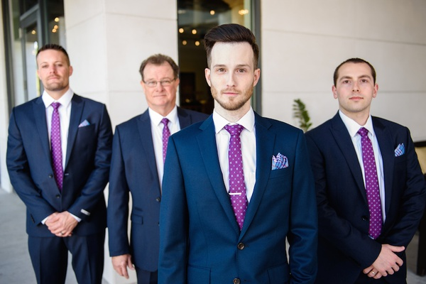 Groom with men in navy suits with polka-dot tie
