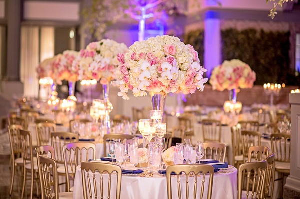 Tall centerpiece with pink rose, white orchid, white hydrangea flowers gold chairs purple lighting
