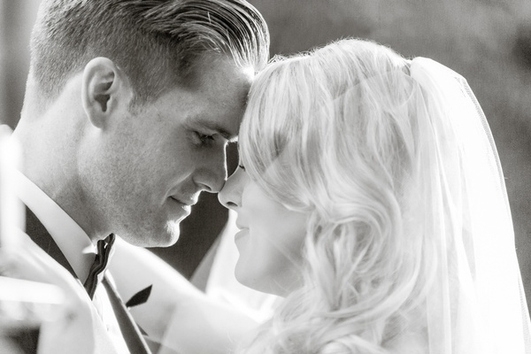 Black and white photo of groom in bow tie with bride in veil touching noses
