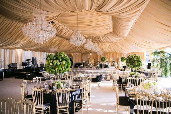 Wedding reception tent gold fabric chandeliers black linens green centerpieces gold chairs
