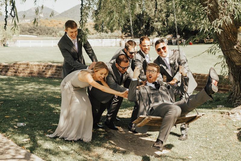 group of groomsmen and groomswoman in grey push groom on wooden swing