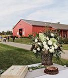 Farm wedding in a red barn, appetizer table with green hydrangeas, white roses, foliage
