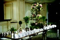 Seating cards on long mirror table with tall flowers