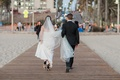 bride carries wedding dress train, groom carries cathedral veil, bride and groom walking on pier