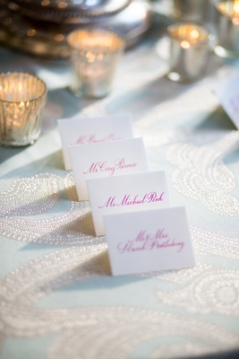 White seating card with hot pink calligraphy