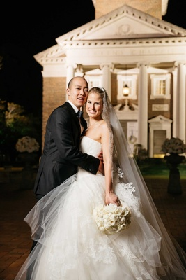 Bride in Vera Wang strapless wedding dress with groom in front of chapel at SMU