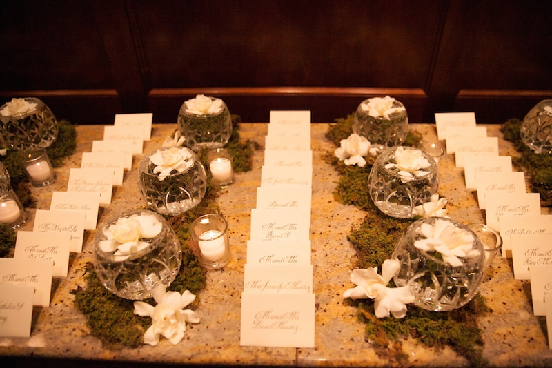Granite table with escort cards, moss, and gardenia flowers