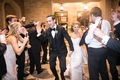 Newlyweds exit venue as guests smile and cheer