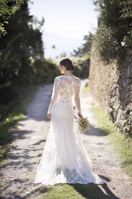 back view of bride standing on dirt road in inbal dror lace wrap wedding dress
