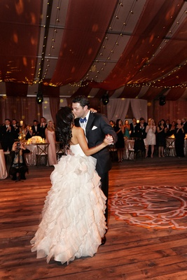 Bride and groom kiss during first dance on rustic dance floor