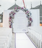 outdoor wedding with ceremony arch featuring blue and purple flowers, white chairs