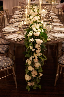 Head table with wood table patterned seat cushions garland of white roses green leaves candles