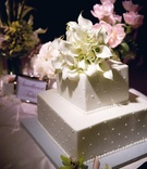White two layer wedding cake with dots and calla lily flowers