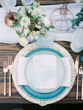 white and blue tablescape with blue plates and white chargers on a wooden table with green florals