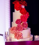 white cake with sugar flowers cascading down side in shades of pink