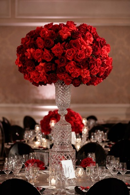 wedding reception decor round table tall crystal centerpiece red flowers roses black guest chairs