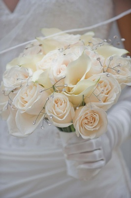 Brides bouquet of light roses and white calla lilies with rhinestones