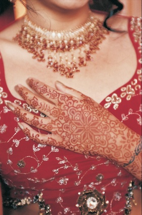 Henna tattoo art on bride's hand over bodice