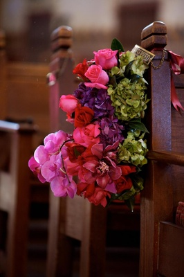 Pink and purple flowers tied to church seating