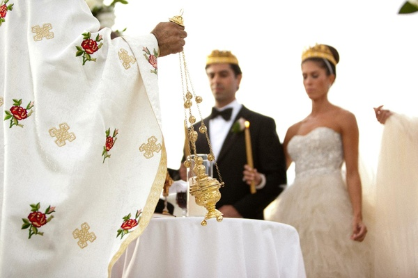 Bride and groom wearing gold crowns at altar