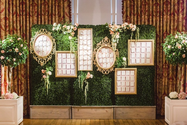 Wedding reception escort cards in gold frames gallery wall on green boxwood hedge wall