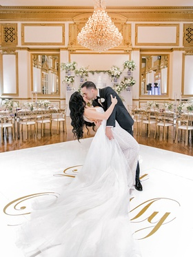 wedding reception ballroom white gold dance floor dip kiss husband and wife wedding