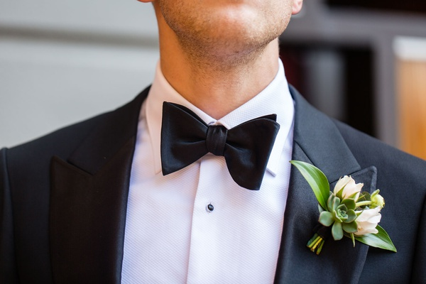 groom in tuxedo and bow tie with succulent white flower green leaf boutonniere
