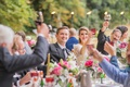 bride and groom at head table with wedding guests toasts colorful goblets pink flowers outdoor