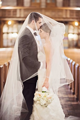 bride and groom embrace under bride's veil groom kisses forehead in chicago church