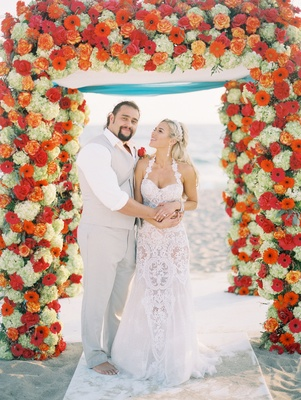 "CJ ""Lana"" Perry and Miroslav ""Rusev"" Barnyashev on wedding day under arch barefoot groom beach"