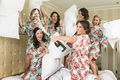bride sprays champagne while bridesmaids in floral robe have pillow fight