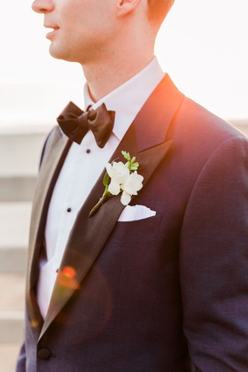wedding portraits groom photo close up of boutonniere white flowers greenery tuxedo bow tie