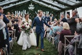 wedding ceremony greenery clear top tent guests in vineyard chairs high five happy couple newlyweds