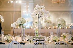 wedding reception flower centerpieces white orchid hydrangea in tall vases white chairs