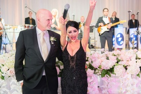 Bride in black beaded designer gown with microphone at wedding reception live band