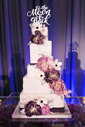 white cake pink and purple floral details to the moon and back tiers blue uplighting