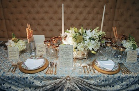 table with blue tablecloth, gold place settings and white flowers