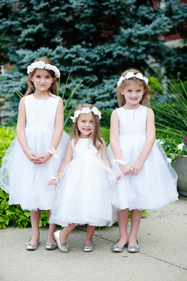 Three flower girls in white dresses, flower crowns, and silver shoes
