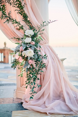 blush drapery on chuppah column with greenery and white and pink flowers