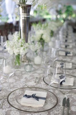 long table with white lace table linens and clear glass plates glasses white and gray place cards