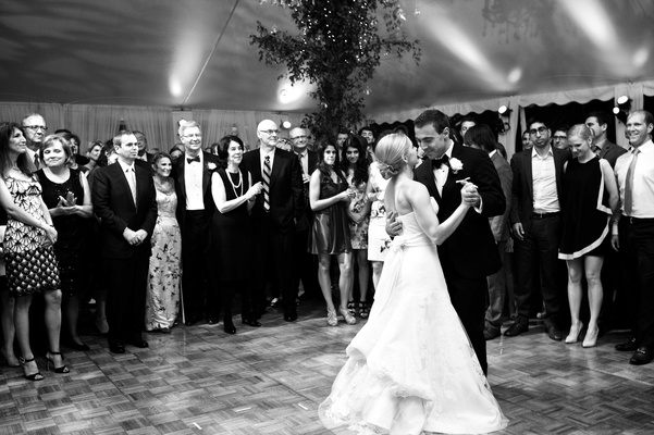 Black and white photo of bride in a strapless Vera Wang dress dancing with groom in a black tuxedo