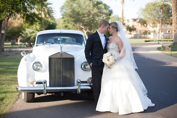 Bride in Anne Barge ball gown and veil with groom in black tuxedo, white Rolls-Royce