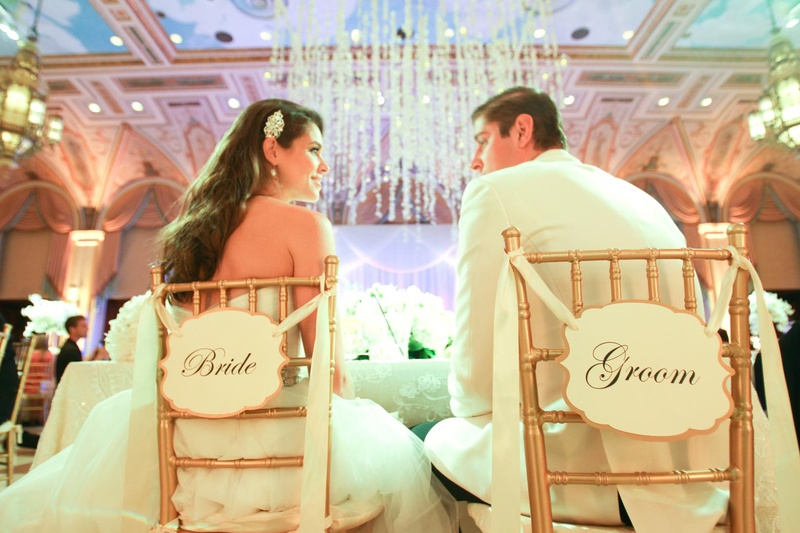 newlyweds sit in chairs with bride and groom signs on the back