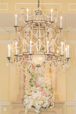Wedding reception with crystal chandelier, arrangement of white, pink, light orange roses, orchids