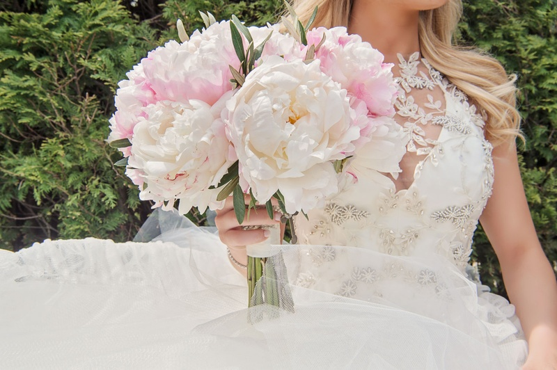 Bride in Vera Wang dress holding pink peony bouquet with rosary of grandmother wrapped around stems