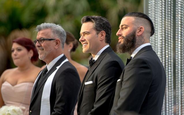 groom in tuxedo smiles as bride walks down the aisle